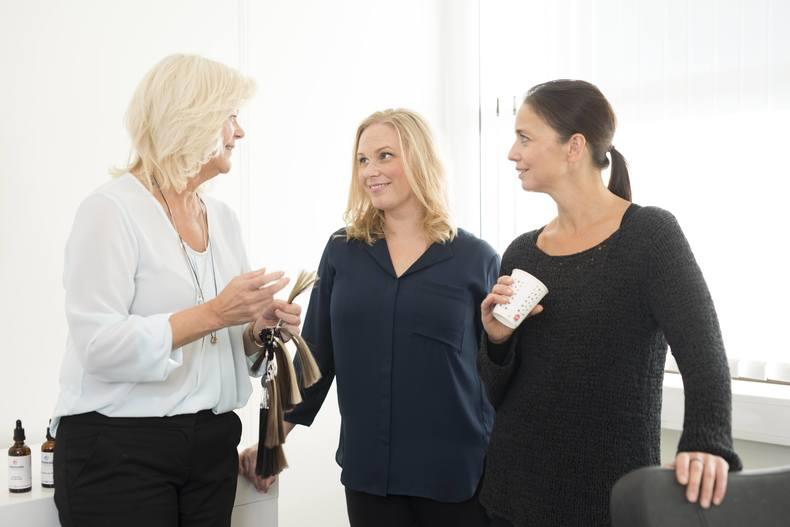 Kvinnelig hårspesialist forklarer to kvinner hvilke løsninger Apollo har for hårtap. To kvinner har blondt, en har mørkt hår.