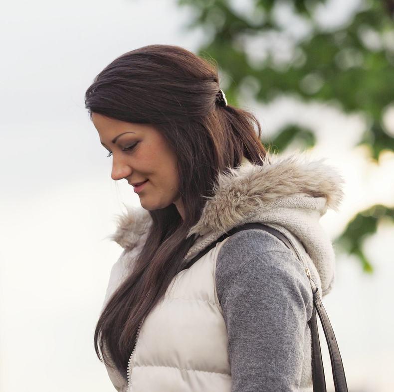 Kvinne i profil med langt mørkt hår, hvit boblevest og grå genser