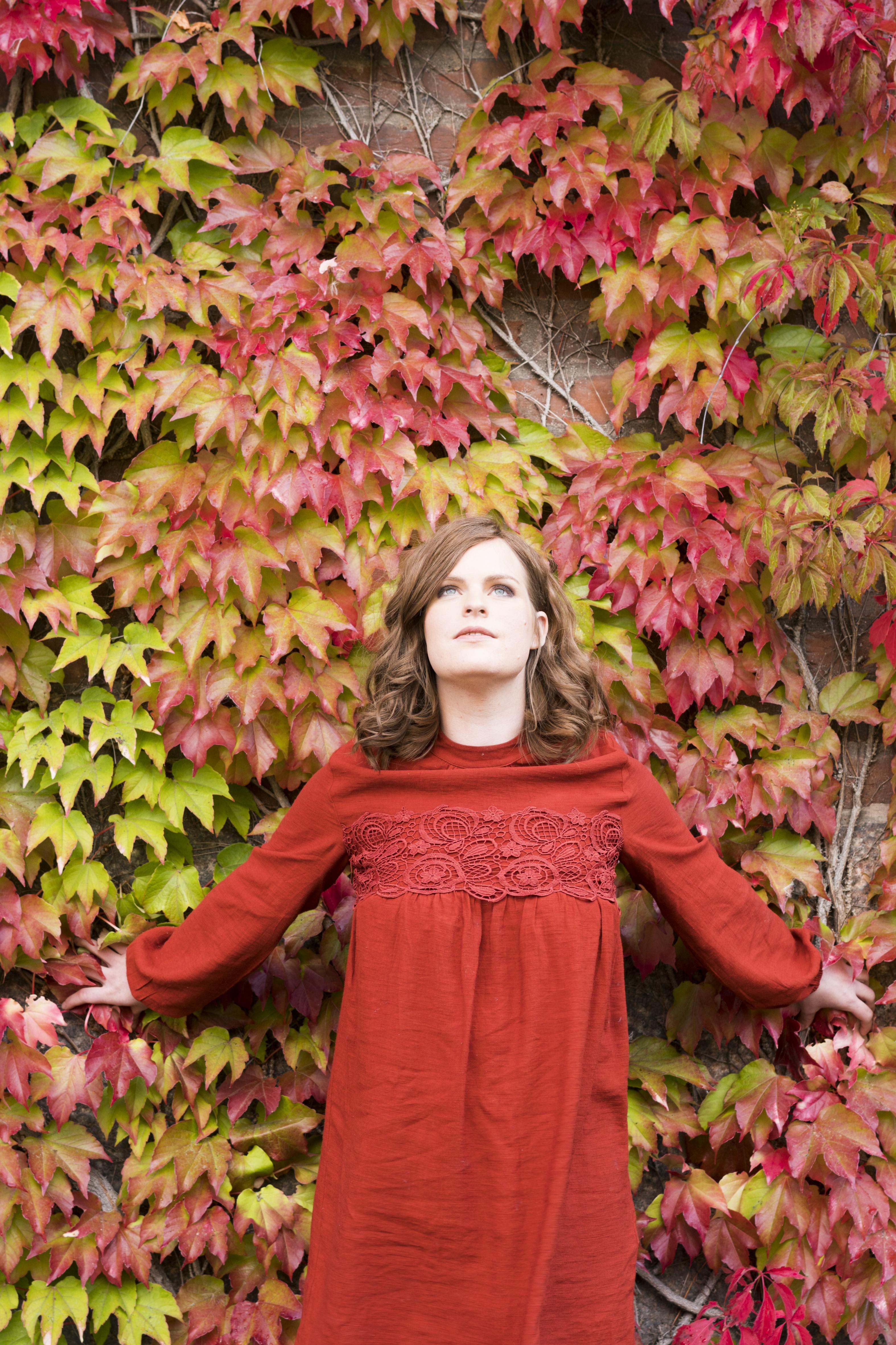Erika bär rött hår i röd klänning framför en vägg täckt av gröna och röda löv