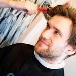 Ung mann med hårdel som blir stelt av frisør.
