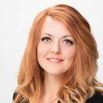 Portrett av ung kvinne med langt, rødt hår. Kvinnen bruker parykk for å løse sitt hårtap.