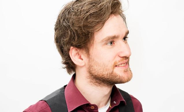 Ung mann i profil som bruker hårdel. Han har skjegg, lilla skjorte og sort vest.